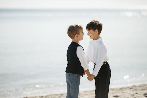 Улыбнувшиеся младшие братья держатся за руки в солнечный день на берегу океана