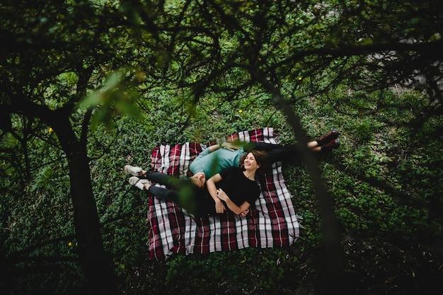 Молодая девушка со своим парнем лежат на пледе в парке