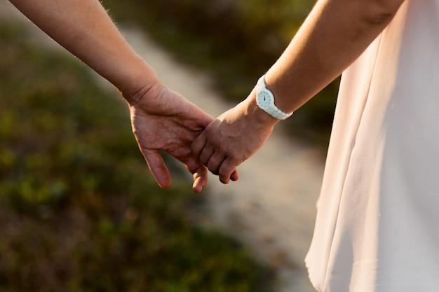 お互いに優しい抱擁のカップルの手を期待してのクローズアップ