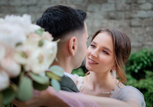 ほとんど屋外でキスしている美しい結婚式のカップルの肖像画