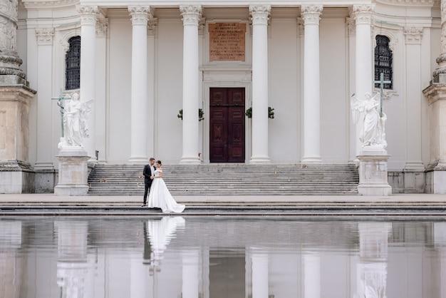 小さな結婚式のカップルが白い柱と水の反射で巨大な大聖堂の近くを歩いています。