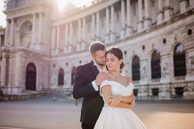 愛の優しいカップルが歴史的な建築物の前で目を閉じて抱いています。