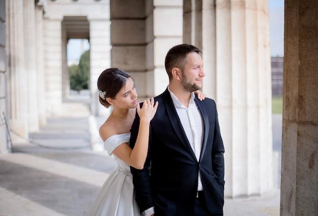 Жених и невеста стоят возле огромной колонны в теплый солнечный день