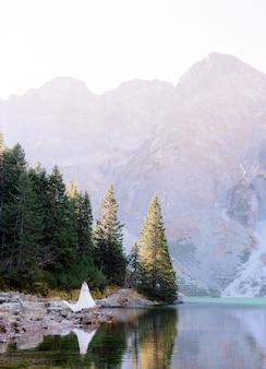 興奮した花嫁が高原の湖と山々の美しさに囲まれて立っています。