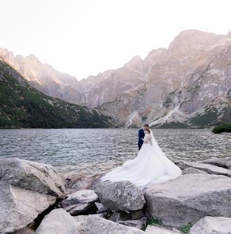 幸せな結婚式のカップルは巨大な岩の山々に囲まれた湖の前に立っています。
