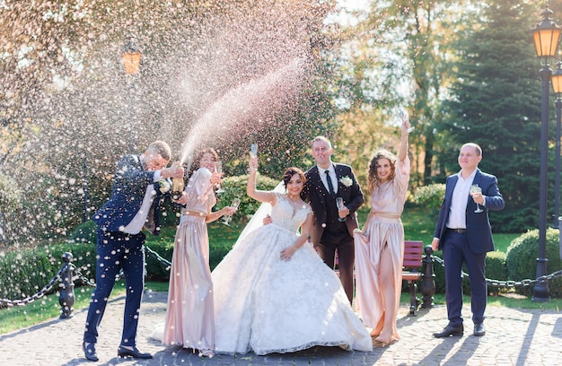 Свадебная пара и лучшие друзья пьют шампанское и празднуют в парке день свадьбы