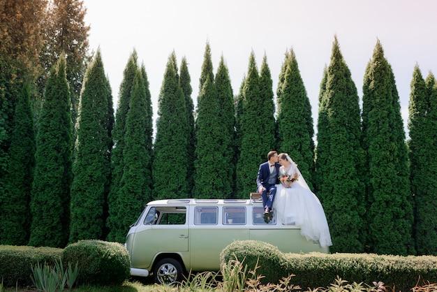 結婚式のカップルは緑の木々に囲まれた屋外の緑のミニバンの屋根の上に座っています。