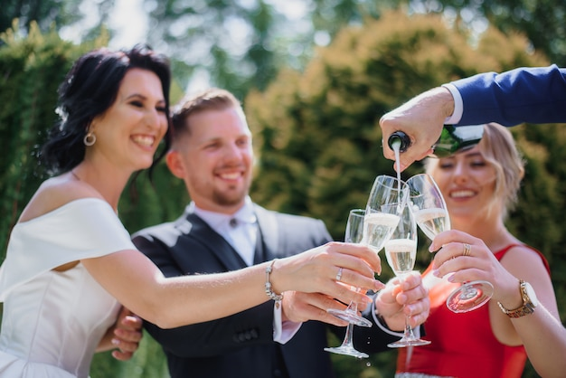 最高の友達と笑顔の結婚式のカップルは屋外でシャンパンを飲んで、笑顔