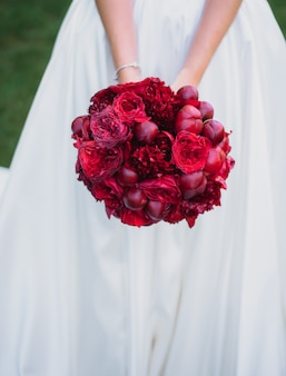 花嫁の手に牡丹で作られた美しい赤いウェディングブーケ
