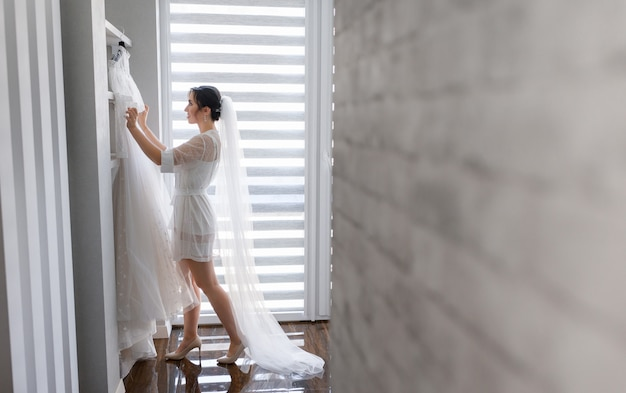 Боковой вид счастливой невесты в длинную вуаль, которая готовится к дню свадьбы в комнате, наряжаясь в свадебное платье