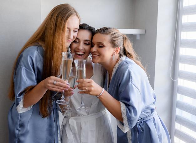 青い絹のようなナイトウェアに身を包んだ笑顔のブライドメイドと花嫁が部屋でシャンパンを飲んでいます。