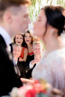 Затуманенное свадьба пара со счастливыми улыбающимися гостями на фоне снаружи