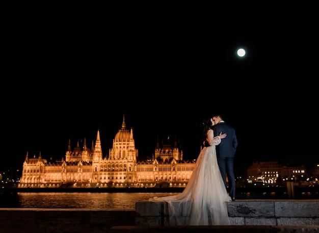 夜のブダペストで絵のように照らされた議会と恋に結婚式のカップルの背面図