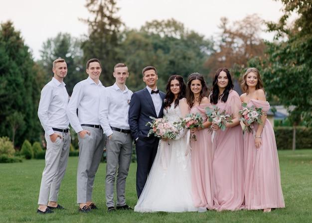 結婚式のカップルとファッショナブルな結婚式の服装に身を包んだ親友が緑の庭に並んでいます。