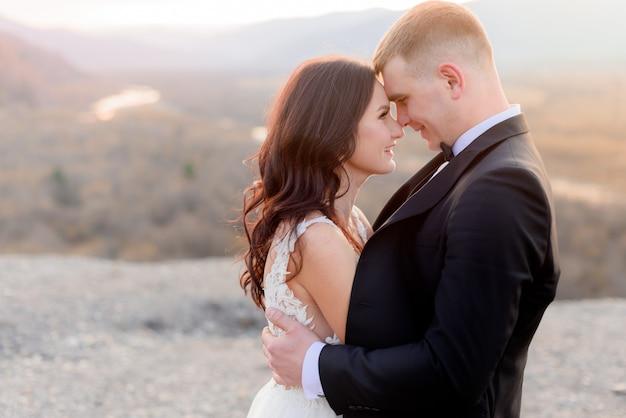 キスの直前の結婚式のカップル、夕暮れ時にお互いを見つめる