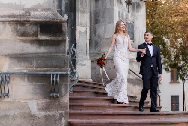幸せな結婚式のカップルが階段の上の教会から出てくる一緒に手を繋いでいます。