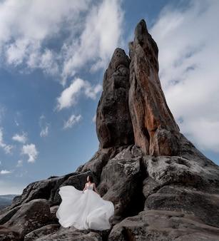 青い空と晴れた日に高い崖の近くの岩の上に美しい花嫁が立っています。