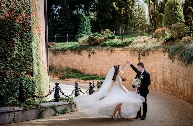 緑のツタで覆われた石の壁の近くで結婚式のカップルが踊っています。
