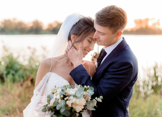 暖かい夜に手で美しいウェディングブーケとほとんどキス水の近くの柔らかい結婚式のカップルの肖像画