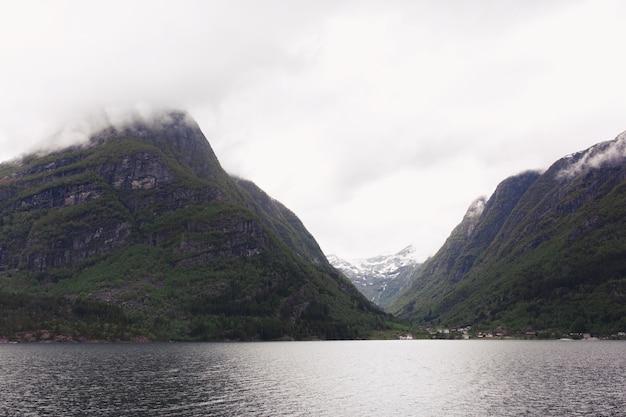 ノルウェーの山々の中の湖に重い雲がぶら下がっている
