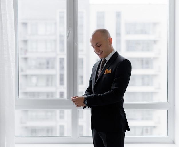 Улыбнувшийся лысый мужчина одевается возле окна в стильный костюм перед важной деловой встречей