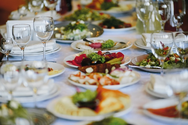 Тарелки с разнообразной едой на праздничном столе