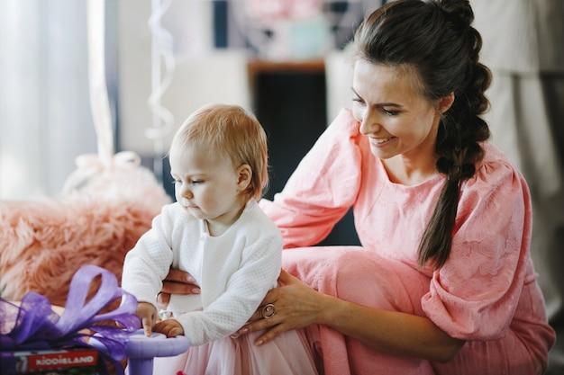 Красивая женщина поддерживает свою маленькую дочь