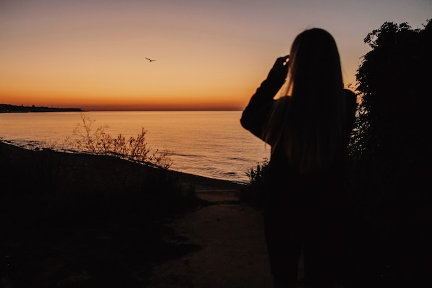 女性は夕方の湖を見ています。