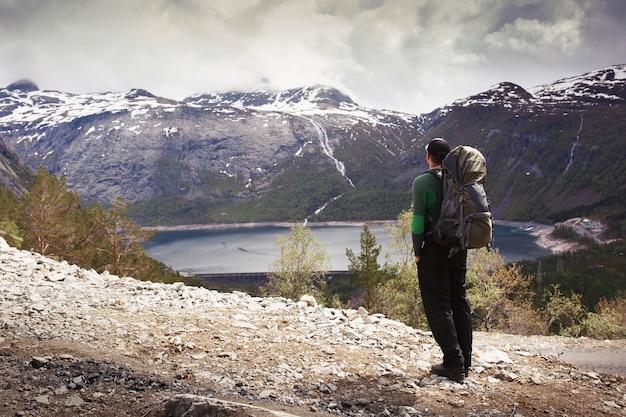 ノルウェーの山々でゴージャスな景色の前に、観光客のリュックサックを持つ男が立っています