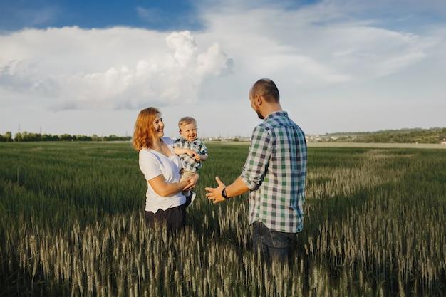 Мать держит своего маленького сына, а отец идет к ним