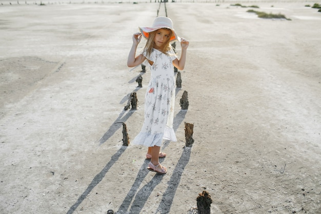 Модная маленькая девочка в летнем белом платье держит края шляпы
