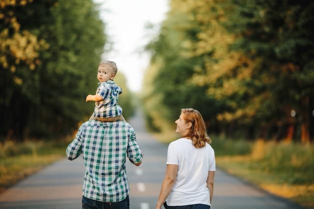 Отец держит сына на плечах, мама рядом