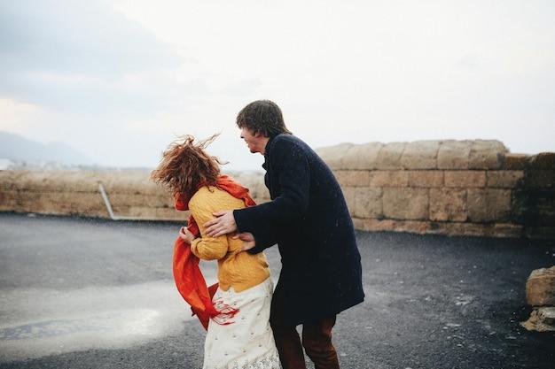 Парень и девушка развлекаются под дождем