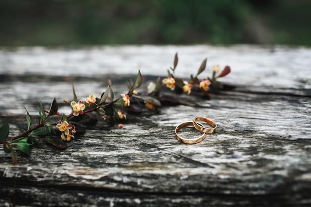 結婚指輪のペアは、花の枝の近くの木製の表面にあります。