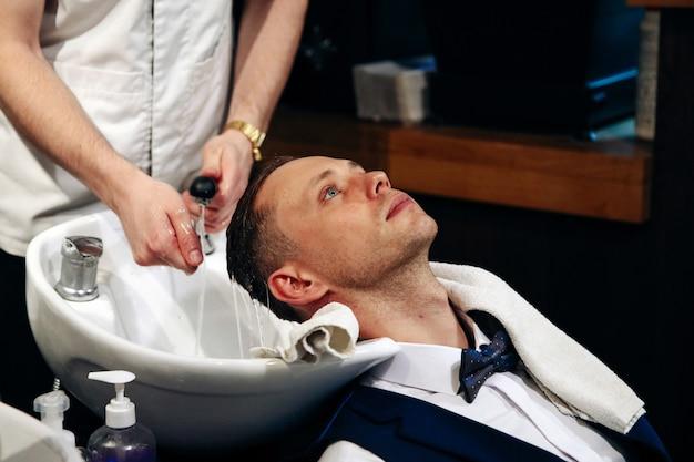 Парикмахер моет мужские волосы