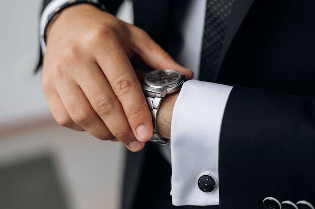 男は手首に時計を見ています