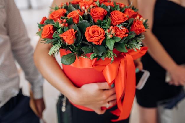 女性は赤いバラと赤いボックスを保持します
