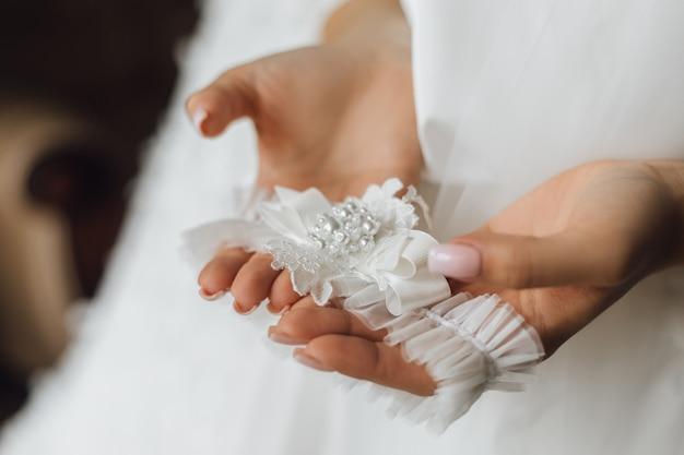 女性は顔のない結婚式のガーターを握る