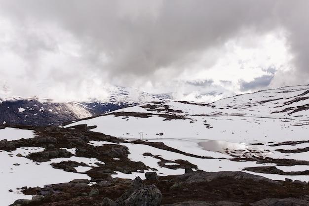 ノルウェーの青い岩の上の雪の前に雪がある