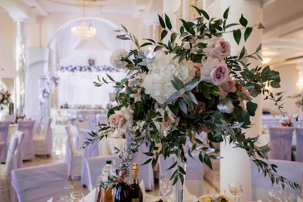 ごちそうのテーブルの上に花と緑で飾られた花束スタンド
