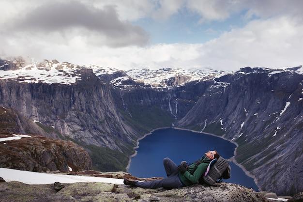 観光客はノルウェーのどこかで山岳湖の美しい景色の前に座っています