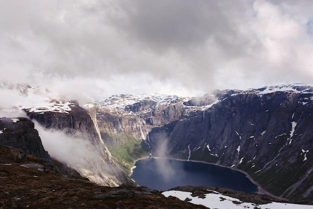 ノルウェーの高い岩の中の青い湖の上を見る
