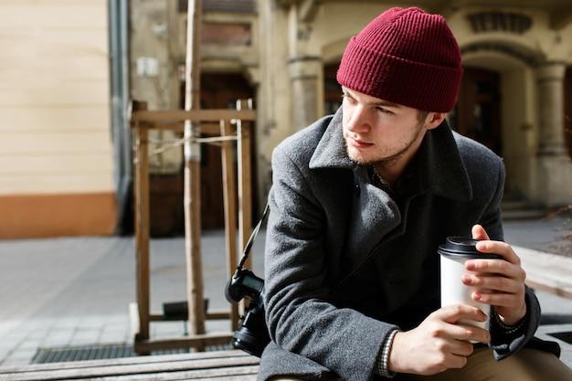 彼の肩にカメラ付きの赤い帽子の少年が通りに座っている