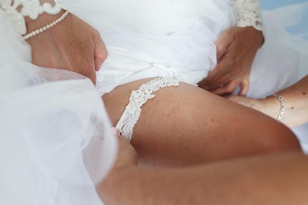 魅惑的な花嫁は白いガーターをかける