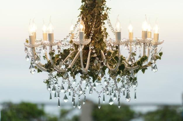 Кристаллы висят от люстры, украшенной зеленью