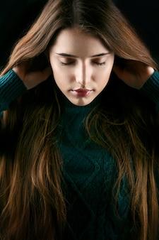 女性は緑のセーターでポーズをとって彼女の髪を保持しています