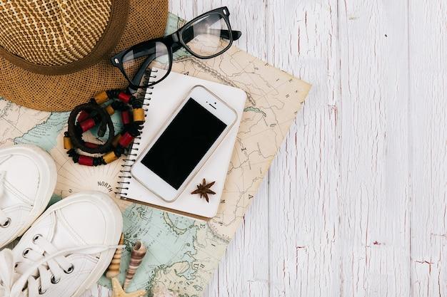 Смартфон лежит на ноутбуке перед картой, шляпой, кедами и очками вокруг нее