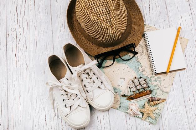 Костюмы, шляпа, очки, блокнот, маленький деревянный корабль лежат на белой карте путешествия