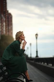 Задумчивая женщина в зеленом платье сидит на скамейке