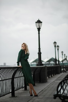 Леди в зеленом платье позирует на набережной в туманный день
